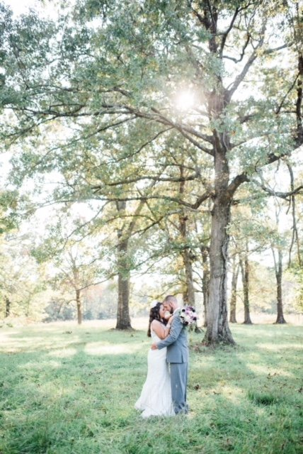 A happy couple hug in front of a tree at Burdoc Farms.