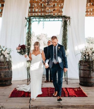 A bride and groom walk down the aisle at Burdoc Frams.