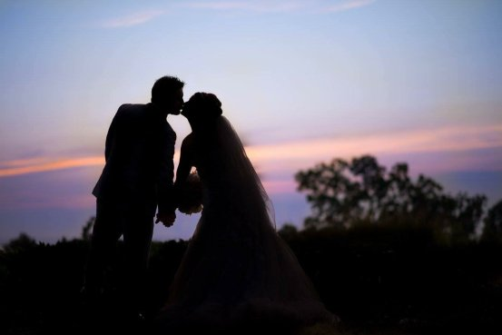 A photo at sunset of a brid and groom kissing