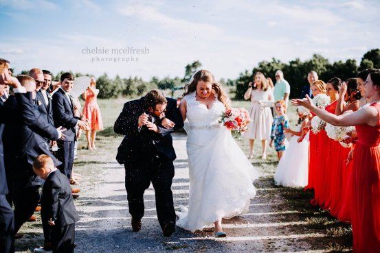 A photo of a bride and groom walking down the aisle at Burdoc Farms
