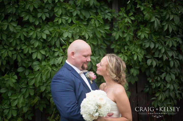 A bride and groom smiling at each other at Burdoc Farms.