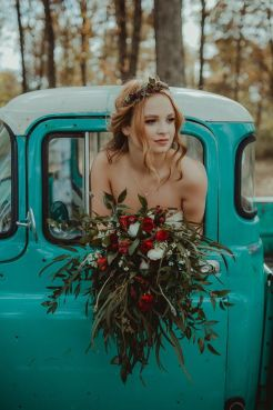 A bride poses with a beautiful floral arrangement.