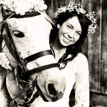 A beautiful bride poses with a horse at Burdoc Farms.