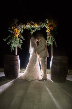 A bride and groom under a floral archway at Burdoc Farms.