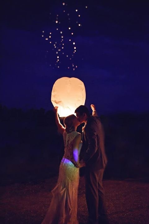 A photo of a bride and groom next to a paper lantern at Burdoc Farms.