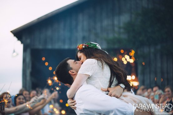 A bride and groom kiss at Burdoc Farms.