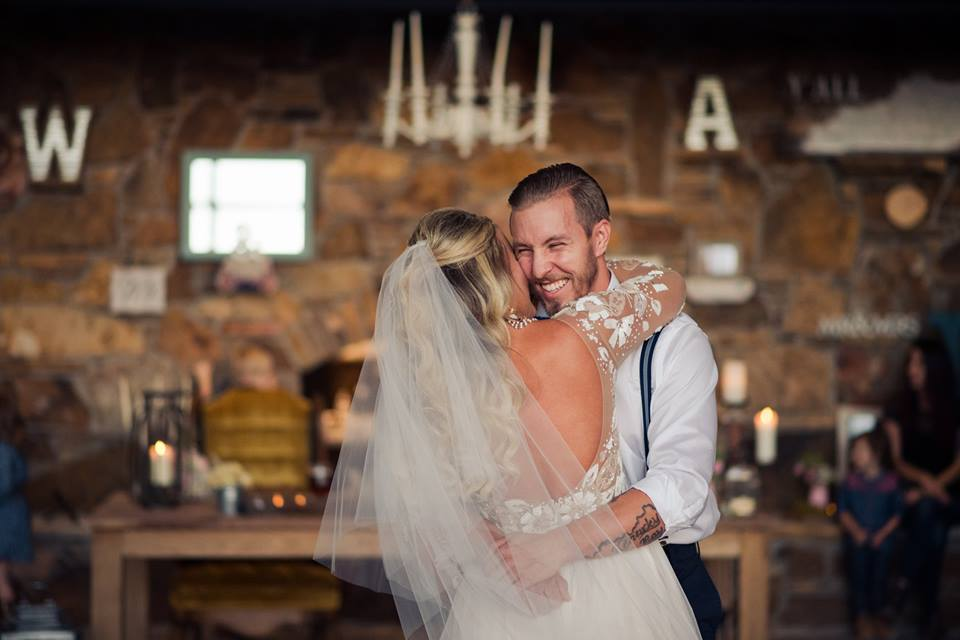 A bride and groom hugging and laughing.