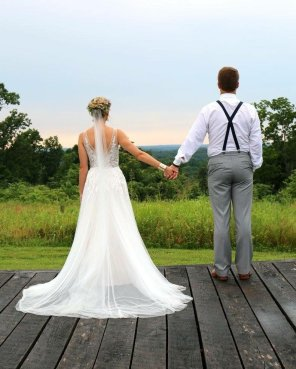 A bride and groom hold hands at Burdoc Farms.